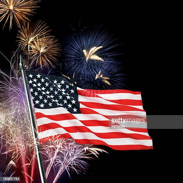 View of the American flag in front of colorful fireworks