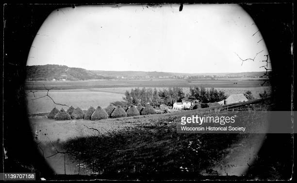 View of the Amund Rustebakke farm Black Earth Wisconsin 1873 Twelve haystacks dominate the center of the image Nearby people stand next to a frame...