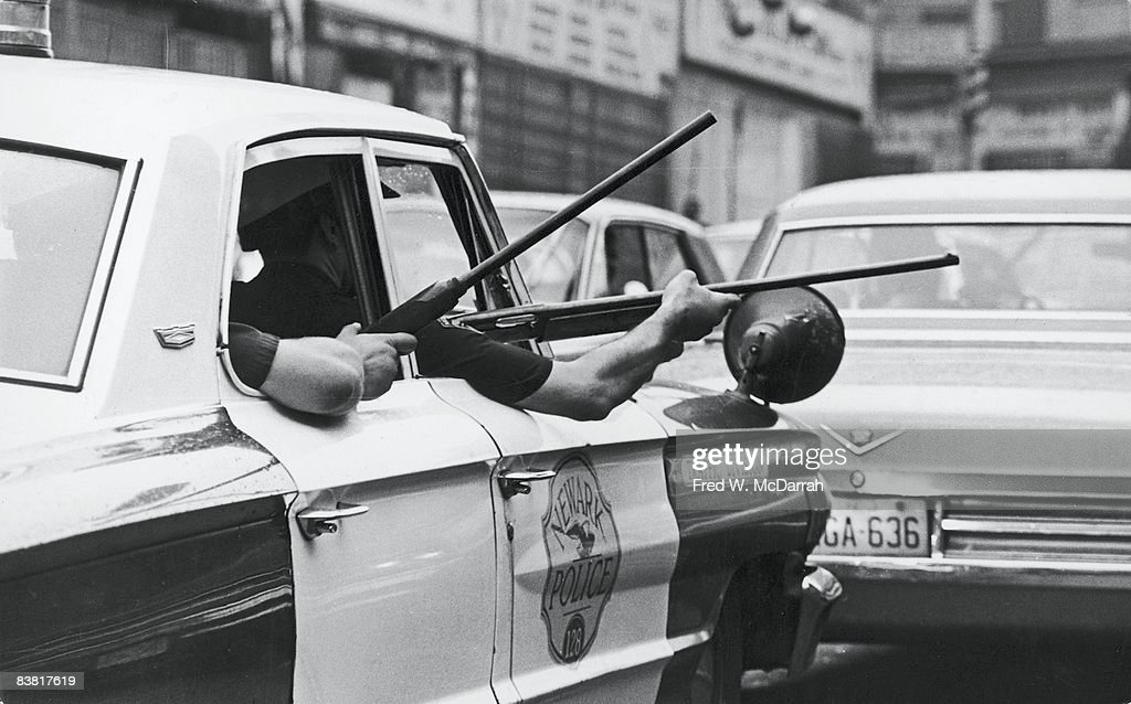 View of the arms of police officers as they hold rifles out of the windows of a police cruiser on Springfield Avenue during the Newark riots, Newark, New Jersey, July 14, 1967. The Newark riots lasted 5 days and resulted in 26 deaths and millions of dollars in property damage.