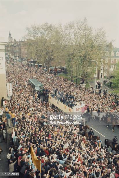 View of the Arsenal football team being transported on the top deck of an open top bus as they parade the FA Cup to supporters lining a street in...