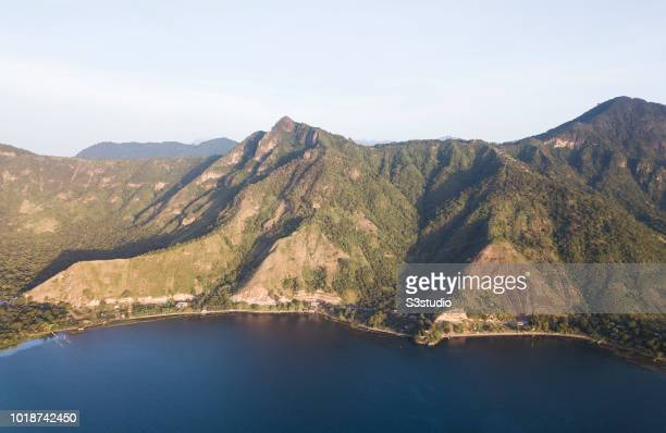A view of the Atitlan volcanoes is seen in the warm light of sunrise at the shores of Lake Atitlan on 12 August 2018 in Guatemala Central America