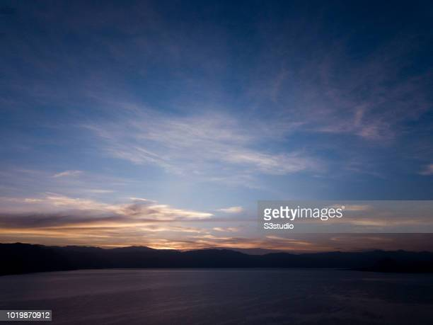 A view of the Atitlan volcanoes is seen in the warm light of sunrise at the shores of Lake Atitlan on 12 August 2018 in the Solola department...