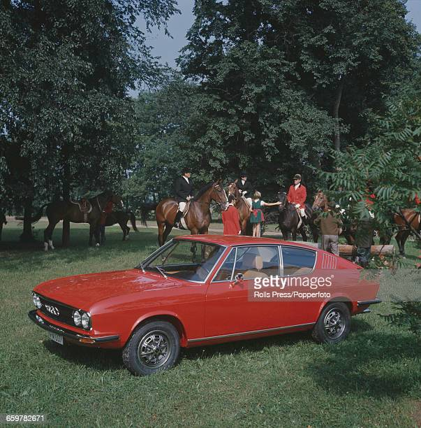 View of the Audi 100 Coupe S fastback coupe car first introduced in autumn 1970 pictured parked on grass in front of huntsmen on horseback