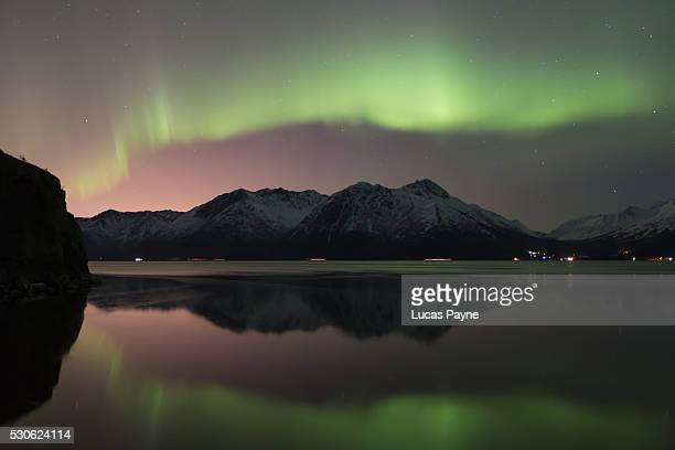 view of the aurora borealis (northern lights) dancing above the chugach mountains and reflecting in the waters of turnagain arm, kenai peninsula; alaska, united states of america - anchorage alaska stock photos and pictures