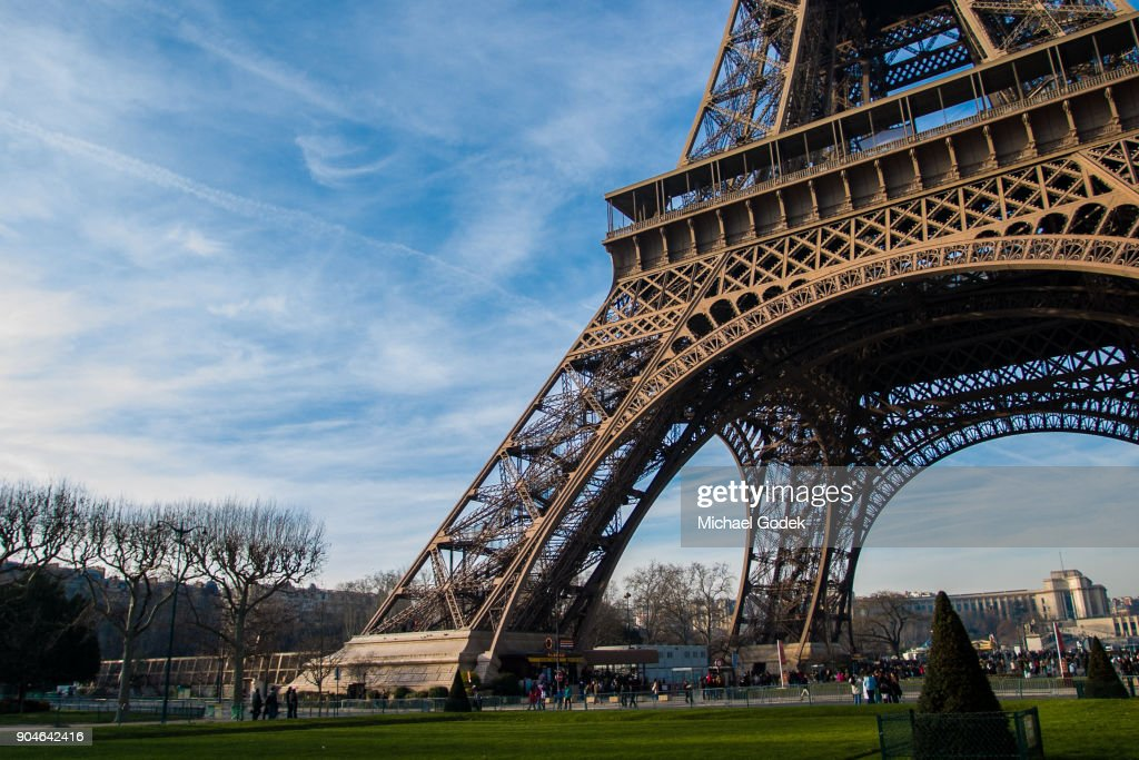 View of the base of the Eiffel Tower with massive feet planted in the ground : Stock Photo