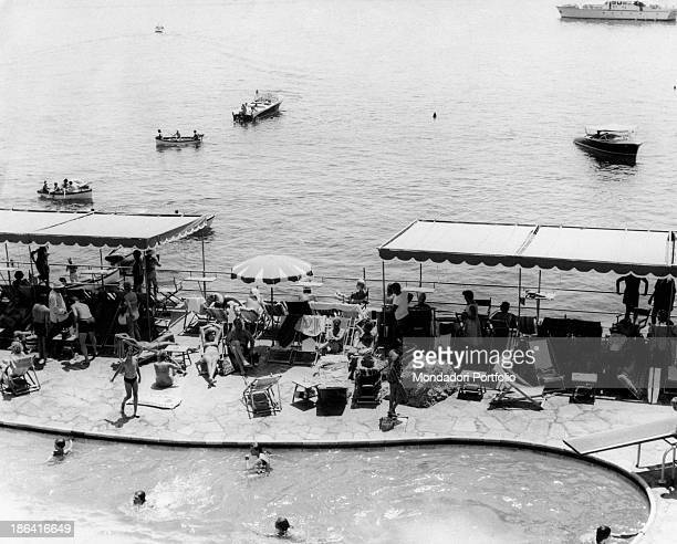 View of the bathing establishment La Canzone del Mare in the bay of Marina Piccola crowded with tourists who sunbathe and bathe in the swimming pool...