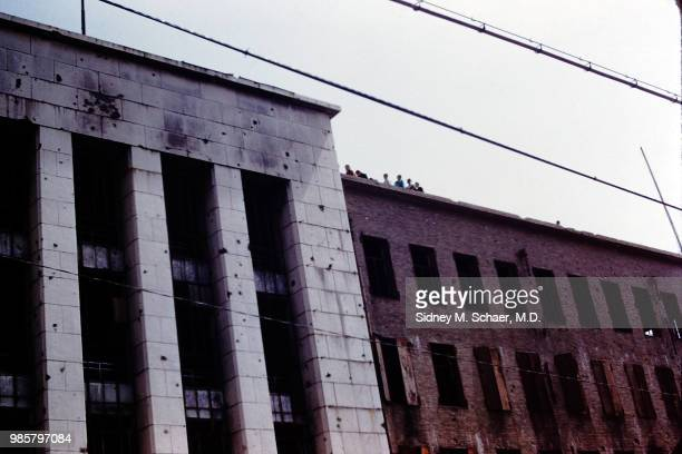 View of the battlescarred facades of a pair of unspecified buildings Seoul South Korea January 1952 A group of people are visible on the roof of one...