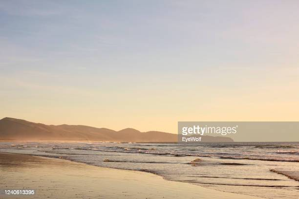 view of the beach in oceanside, oregon during low tide at sunset - beige stock pictures, royalty-free photos & images