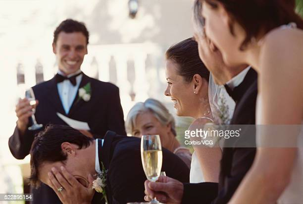 View of the best man embarrassing the groom during his speech at a wedding reception