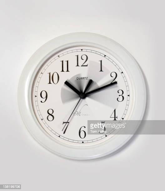 View of the blurred hands of a white clock on a white wall June 6 2001
