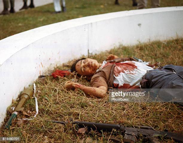View of the body of a dead Viet Cong soldier several weapons nearby on the grounds of the American Embassy during the Tet Offensive Saigon Vietnam...