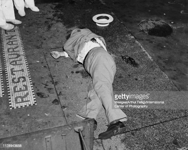 View of the body of gangster Dominick Didato on the sidewalk outside a restaurant on Elizabeth Street New York August 6 1936 His hat and a revolved...