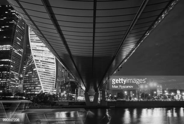 view of the bottom of the pedestrian bridge over the river with skyscrapers in the background at night - financiën en economie stockfoto's en -beelden
