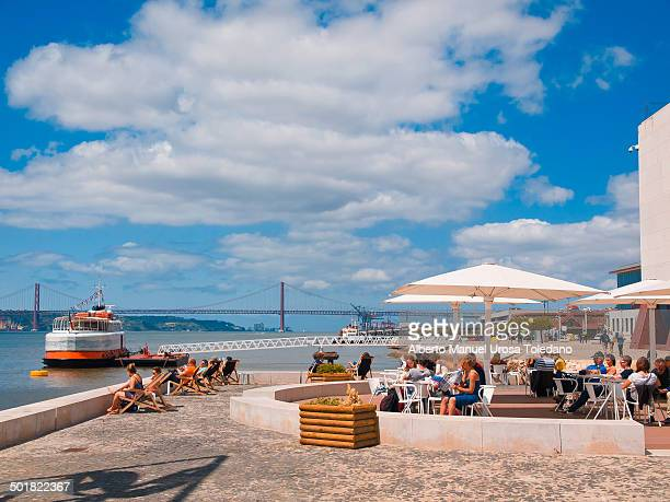 """View of the bridge """" 25 de Octubre"""" that it links both banks of the Tagus or Tejo River in the riverbanks near to Cais do Sodre and a few tourists..."""