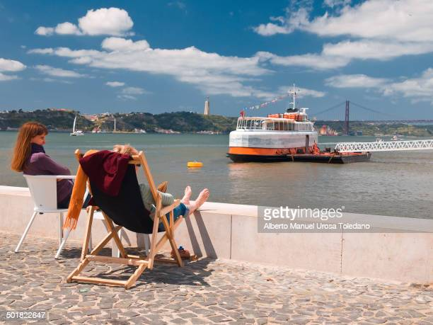 """View of the bridge """"25 de Octubre"""" that links both banks of the Tagus or Tejo River in the riverbanks near to Cais do Sodre and a few tourists..."""