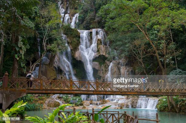 View of the bridge with people in front of the upper larger waterfall of the Kuang Si Falls near Luang Prabang in Laos