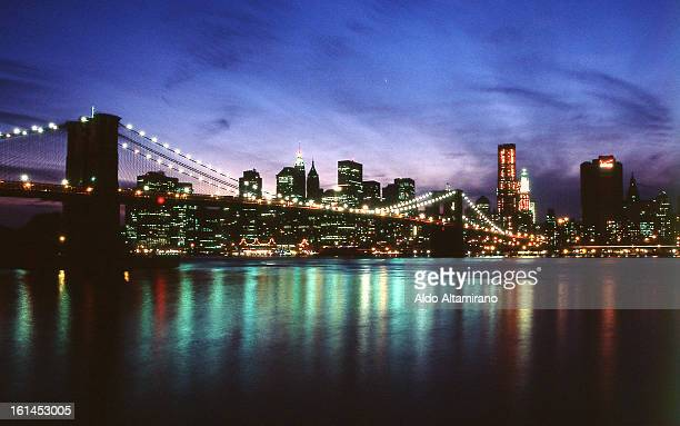 View of the Brooklyn Bridge, East River and Manhattan Downtown from Dumbo in Brooklyn at dusk. Cityscape, nigh, cloudy sky, skyline, lights,...