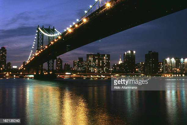 CONTENT] View of the Brooklyn Bridge East River and Manhattan skyline from Dumbo section of Brooklyn New York night East River light lights bridge...