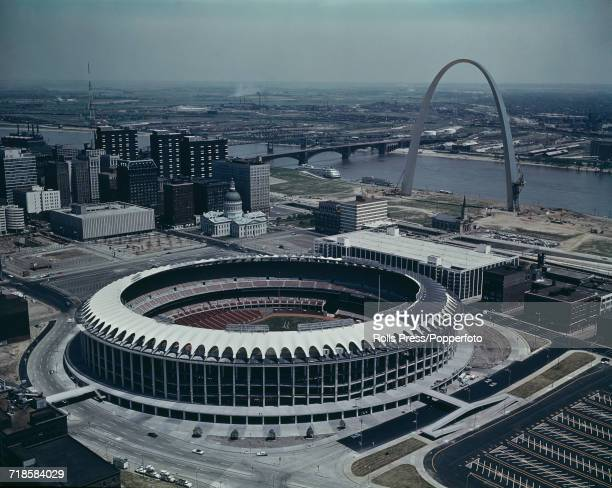 View of the Busch Memorial Stadium, pictured soon after construction in 1966, with the Gateway Arch monument and Mississippi River in the background,...
