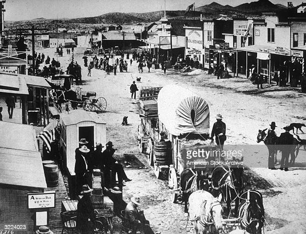 View of the busy main street in the western settlement of Tomapah Nevada Horsedrawn covered wagons bring goods to trading posts as men sit and walk...