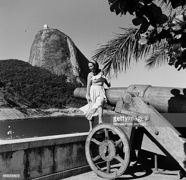 A view of the cable car on Sugarloaf Mountain as A woman poses on a canon in Rio de Janeiro Brazil