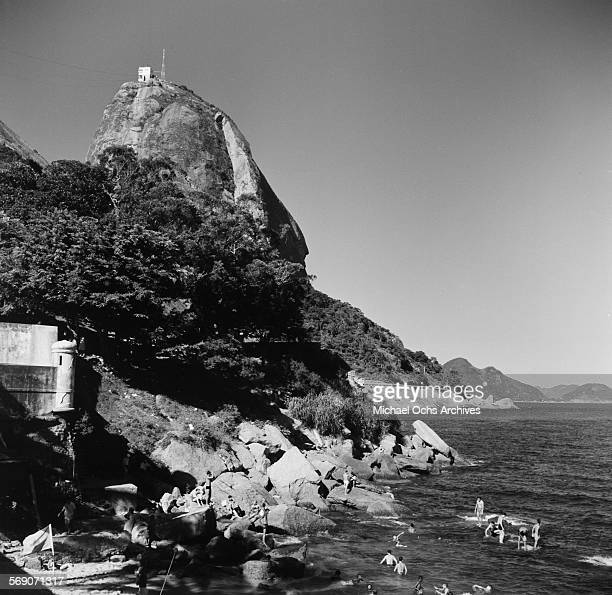 A view of the cable car on Sugarloaf Mountain as people swim in the ocean in Rio de Janeiro Brazil