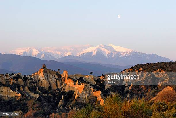 View of the Canigou massif and the hoodoos called 'les Orgues' in IllesurTet at sunset The snowcapped summit of Canigou and the moon Rock...