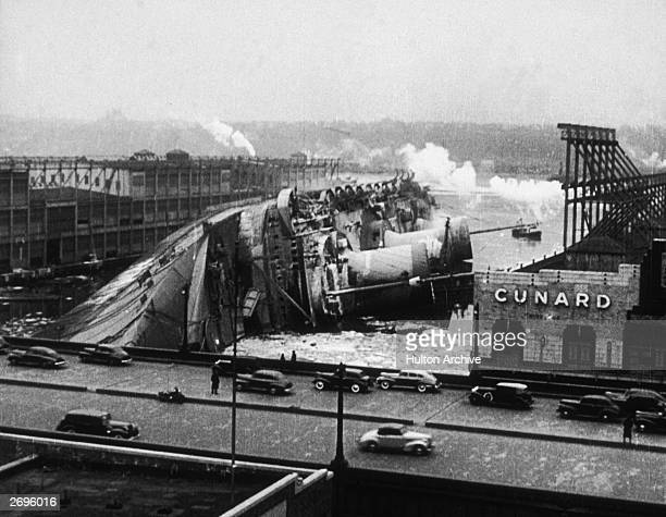 View of the capsized French ocean liner the Normandie laying on its side in port after it caught fire and began to sink New York City Several people...