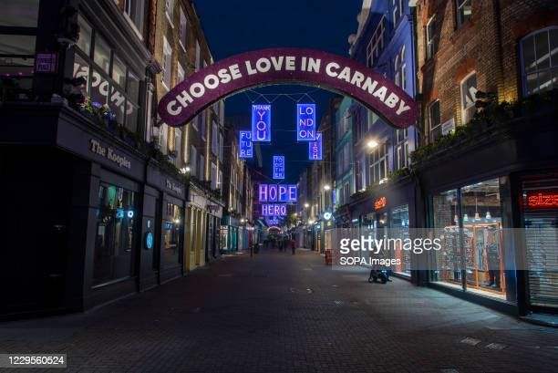 View of the Carnaby Street Choose Love Christmas illuminated signs created in collaboration with the Choose Love charity. Pink neon lights from a...