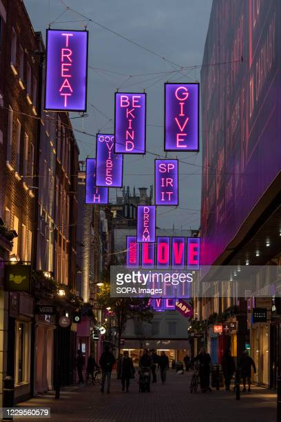 View of the Carnaby Street Choose Love Christmas illuminated signs with created in collaboration with the Choose Love charity. Pink neon lights from...