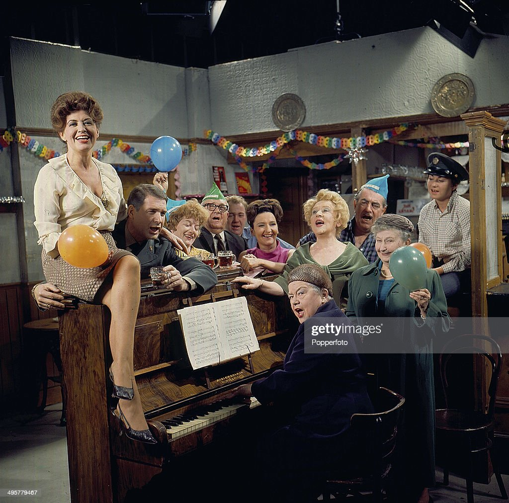 View of the cast of the television soap opera 'Coronation Street' in a Christmas scene around an upright piano in 1968. Actors in the scene include Pat Phoenix as 'Elsie Tanner', Violet Carson as 'Ena Sharples', Bernard Youens as 'Stan Ogden', Jean Alexander as 'Hilda Ogden', Doris Speed as 'Annie Walker' and Jack Howarth as 'Albert Tatlock'.
