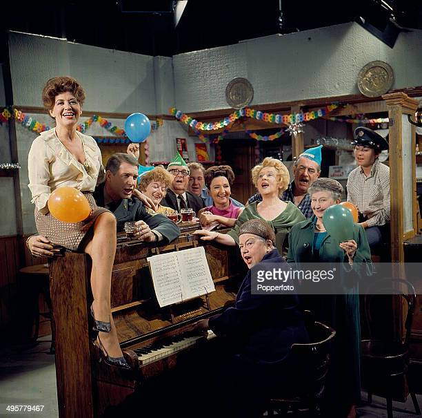 View of the cast of the television soap opera 'Coronation Street' in a Christmas scene around an upright piano in 1968 Actors in the scene include...