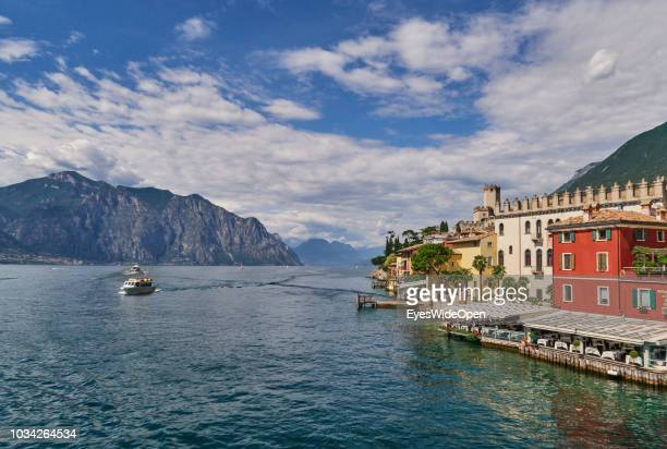 View of the castle city and mountains from a ferry boat at the northern part of the Lake Garda on June 29 2018 in Malcesine Italy