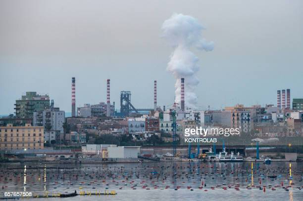 View of the central part of the Ilva Taranto plant behind the Tamburi populous district with an intense white smoke Italian steel mill with the...