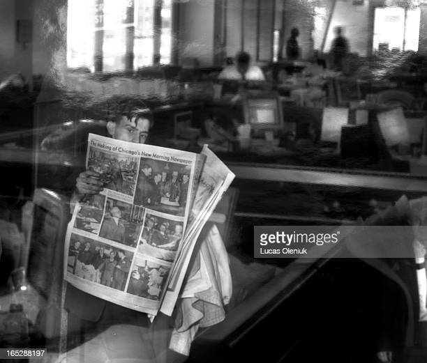A view of the Chicago Sun Times newsroom reflected in an old black and white print that shows a man reading a newspaper describing the making of...