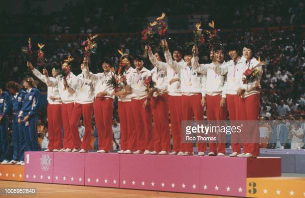 View of the China female volleyball team standing together on the medal podium after finishing in first place to win the gold medal in the Women's...