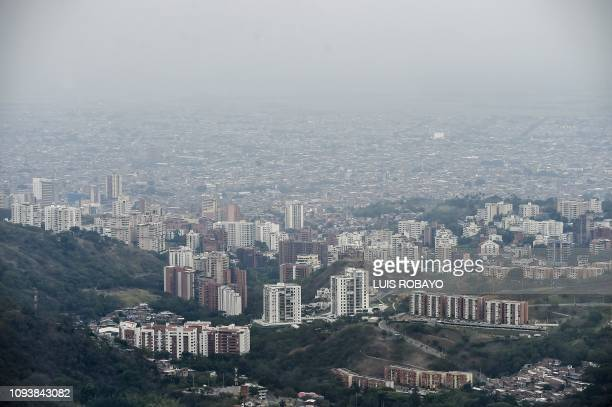 View of the city of Cali through smoke from a forest fire on February 4 2019 in a rural area near Cali Colombia The fire that broke out on Saturday...
