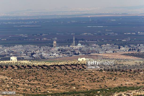 View of the city of Daraa in Syria as seen from the Jordanian side as refugees fleeing the conflict in Syria arrive to the Jordanian border at a safe...
