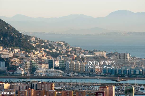 View of the City of Gibraltar from La Línea de la Concepción, Spain, with Morocco and the Rif Mountains in the distance.