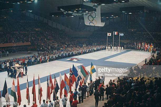 View of the closing ceremony of the 1968 Winter Olympic Games with flag bearers of competing countries standing together inside Le Stade de Glace...
