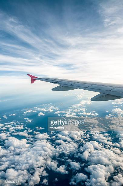 View of the cloudy sky and left airplane wing from a window
