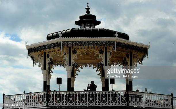 A view of the conductor leading a band playing on the bandstand on the seafront in Hove East Sussex
