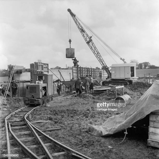 View of the construction of a structure, probably on Section B of the Birmingham to Preston Motorway , showing an engine on a narrow gauge railway, a...