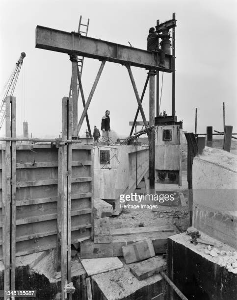 View of the construction of the Birmingham to Preston Motorway , showing a worker watching another worker adjusting 200-ton jacks in preparation for...