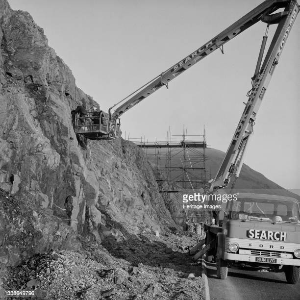 View of the construction of the M6 Motorway through the Lune Gorge, showing two men in a truck-mounted hydraulic lifting platform, working against a...