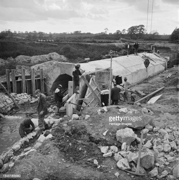 View of the construction of the Midland Link Motorway, between Junction 13 and Junction 11 of the M6, showing a team of workers gathered around a...