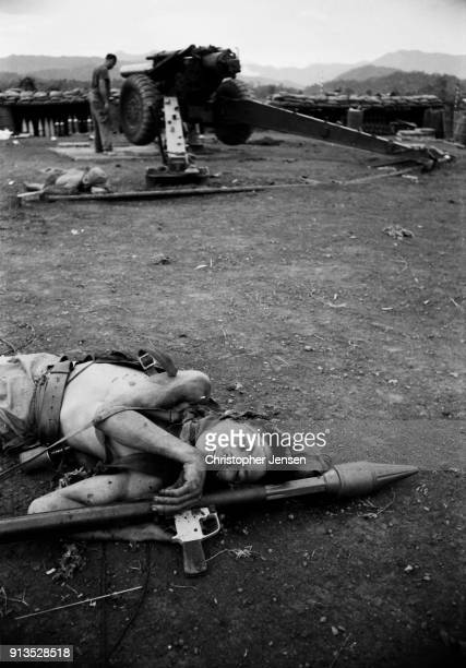 View of the corpse of an NVA commando near a US M114 155 mm howitzer at a small US base Kham Duc Republic of Vietnam August 5 1970 His...