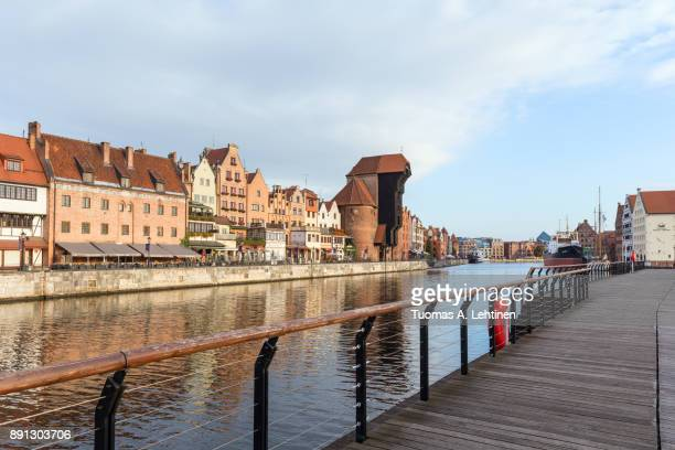 View of the Crane and other old buildings along the Long Bridge waterfront, Motlawa river and wooden boardwalk at the Main Town in Gdansk, Poland, in the morning.
