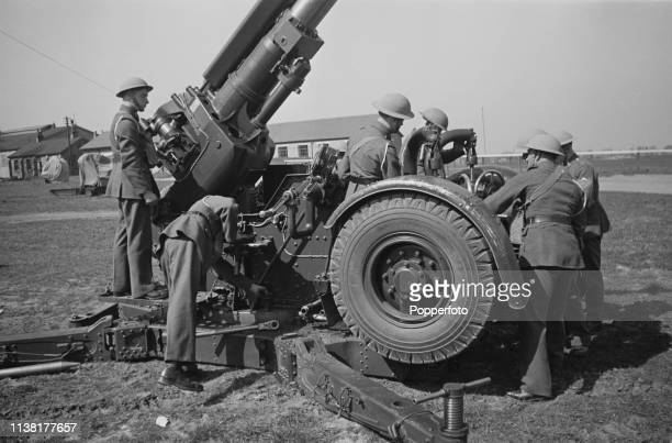 View of the crew of a British Army Vickers QF 3.7 inch anti-aircraft gun placing the mobile version in to defensive position at Royal Air Force...
