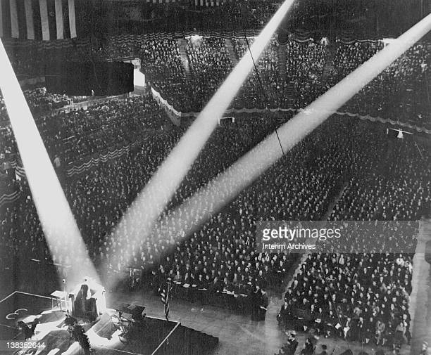 View of the crowd and stage at a wartime rally organized by the Wholesale and Warehouse Workers Union at Madison Square Garden New York early to mid...
